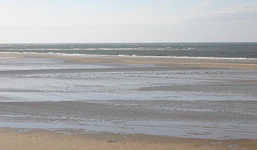 Ebbe und Flut in der Nordsee vor Niedersachsen - Sandstrand bei einsetzender Flut